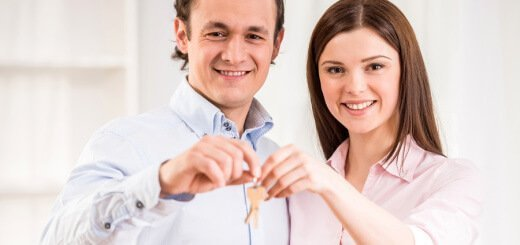 Happy young couple with keys in their new apartment.